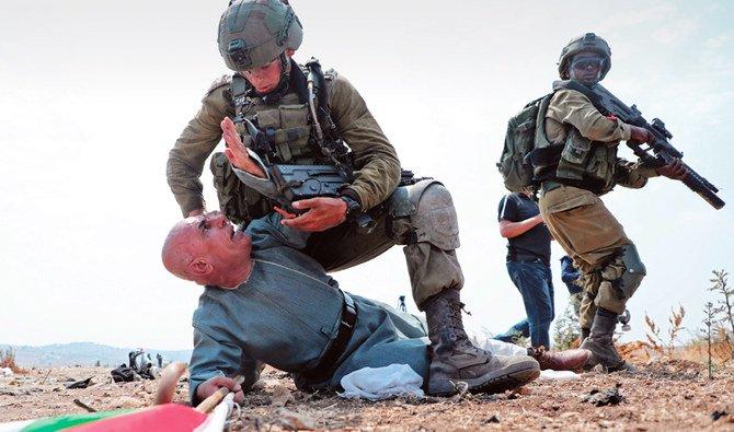 Gambar orang Palestina di bawah lutut tentara Israel memicu kemarahan